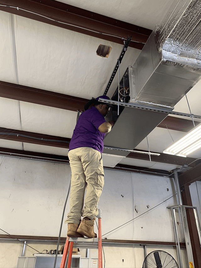 HVAC technician working on air ducts